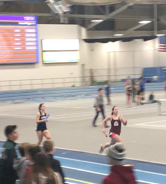 In the 4x200 meter relay, freshman Claire Kurja races in a close sprint behind Amesbury.