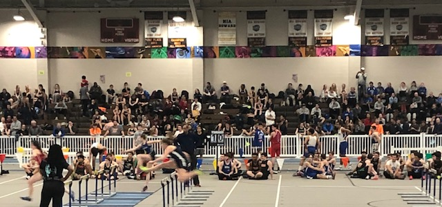 The 55 meter hurdle relay has sophomore Lily Waterman in position for a strong finish.
