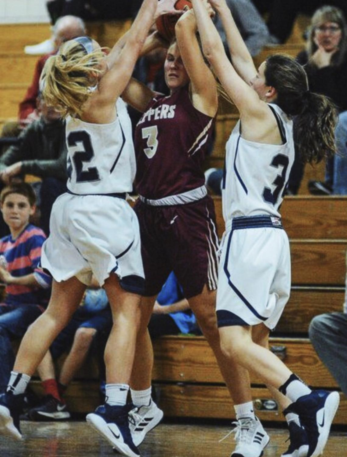 Maddy Rivers(left) jumping up to get the ball away from Newburyport