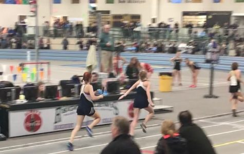 Junior Tess Contois passes the baton  off to sophomore Gaylan Ryuss in the 4x200 meter relay.