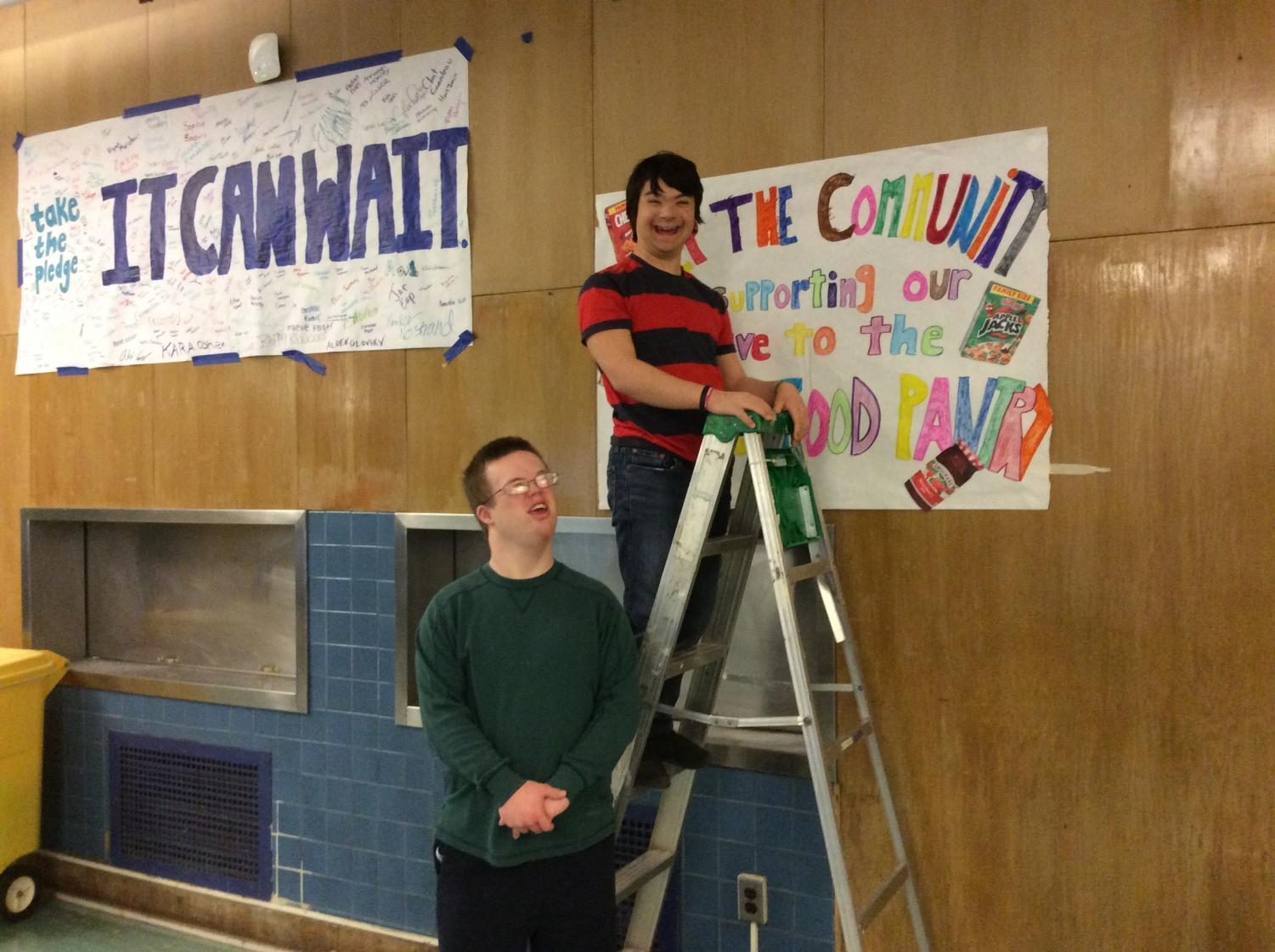 Timothy LaBudde ('21) on left and Max Vanderwilden ('21) on right hang up the poster announcing the food drive.