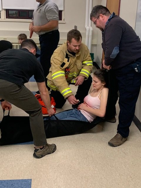 Hamilton-Wenham police and firemen practice administering aid to student volunteers.