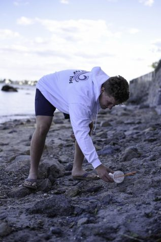 Christopher Domoracki reaches down to pick up garbage polluting Old Garden Beach in Rockport.